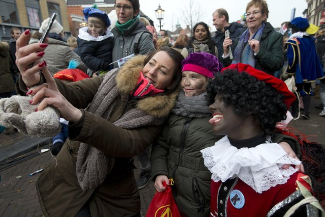 A mother takes a selfie with her daughter and a Black Pete during the arrival of Sinterklaas, the Dutch Saint Nicholas, in Maassluis, Netherlands, Saturday, November 12, 2016. Sinterklaas and his helper Black Pete are at the center of a long-time controversy because Pete is often played by white people in blackface makeup. (Photo by Peter Dejong/AP Photo)
