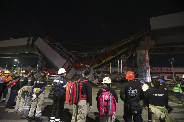 Rescue personnel stand in front of Mexico City subway cars laying at an angle after a section of Line 12 of the subway collapsed in Mexico City, Tuesday, May 4, 2021. (Photo by Marco Ugarte/AP Photo)