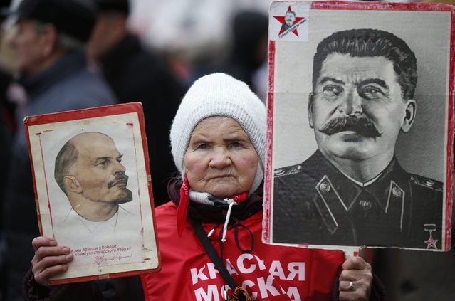 A supporter of the Russian Communist party holds portraits of Soviet state leaders Vladimir Lenin (L) and Josef Stalin during a procession to mark the Defender of the Fatherland Day in central Moscow February 23, 2015. (Photo by Maxim Zmeyev/Reuters)