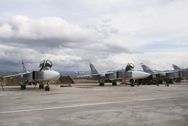 A line-up of Russian bombers stand on tarmac as another plane takes off in the background at Hemeimeem air base in Syria on Wednesday January 20, 2016. (Photo by Vladimir Isachenkov/AP Photo)