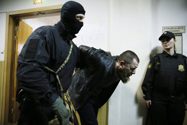 Tamerlan Eskerkhanov (C), detained over suspicion in the killing of opposition politician Boris Nemtsov, is escorted to a court room at the Basmanny City Court in Moscow, Russia, 08 March 2015. Five people which the investigation believes to be involved in Nemtsov's killing have been arrested.  EPA/YURI KOCHETKOV