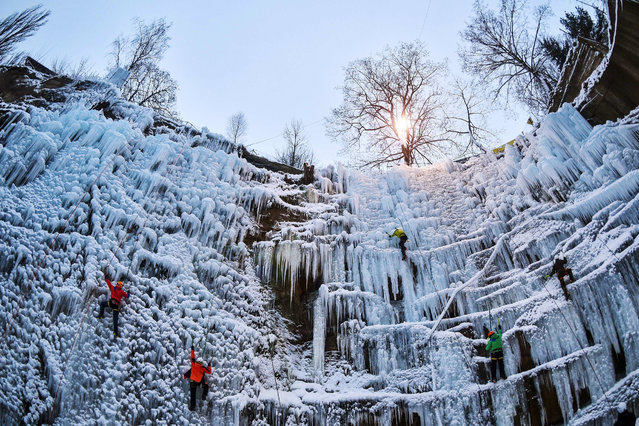 People climb on an artificial ice-wall in Liberec, about 100 km north of Prague, Czech Republic, Saturday, January 23, 2015. The wall was prepared in a former quarry just near the centre of the city. (Photo by Radek Petrasek/CTK via AP Photo)