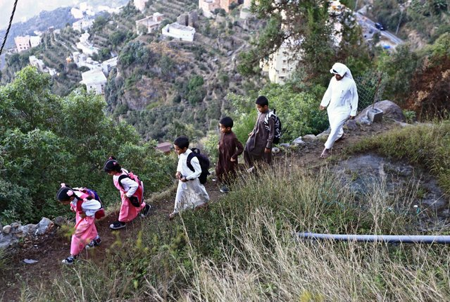 Saudi man Yazid al-Fefi walks with his children as they make their way to their schools through Fifa Mountain, in Jazan, south of Saudi Arabia, December 15, 2016. (Photo by Mohamed Al Hwaity/Reuters)