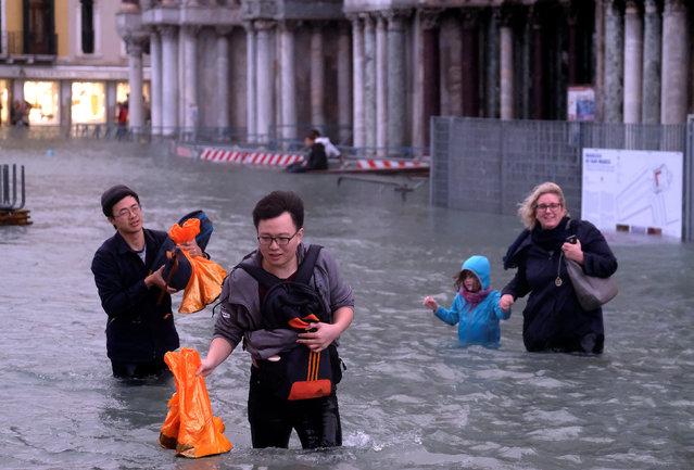 People walk in a flooded Saint Mark Square during a period of seasonal high water in Venice, Italy on October 29, 2018. (Photo by Manuel Silvestri/Reuters)
