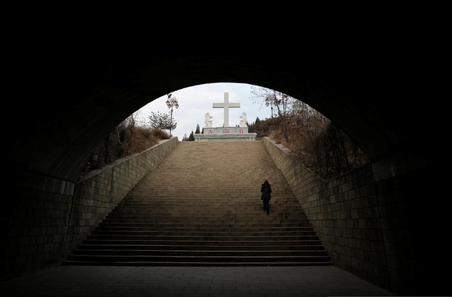 A villager climbs up the steps toward a cross near a Catholic church on the outskirts of Taiyuan, North China's Shanxi province, December 24, 2016. (Photo by Jason Lee/Reuters)