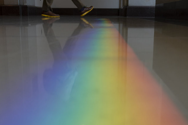 A rainbow is projected on the floor by the sun passing through windows of the Capitol Visitor Center area of the U.S. Capitol in Washington, Wednesday, June 23, 2021. (Photo by Alex Brandon/AP Photo)