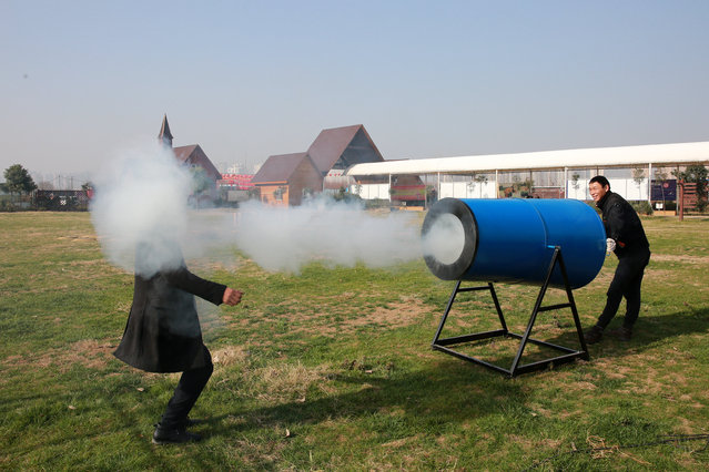 "People demonstrate a home-made ""smog cannon"" which fires cannonballs made of ""water and tobacco tar"" to remind people the importance of protecting environment, in Xiangyang, Hubei province, December 27, 2016. (Photo by Reuters/Stringer)"