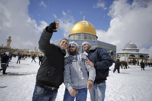 Palestinian men take a photograph in front of the snow-covered Dome of the Rock on the compound known to Muslims as Noble Sanctuary and to Jews as Temple Mount, in Jerusalem's Old City February 20, 2015. (Photo by Ammar Awad/Reuters)