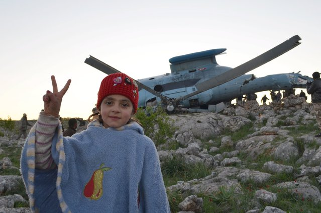 A girl flashes a victory sign as she poses near a helicopter that belongs to forces loyal to Syria's President Bashar Al-Assad after it crashed in Jabal al-Zawiya in the southern countryside of Idlib  March 22, 2015. (Photo by Abed Kontar/Reuters)