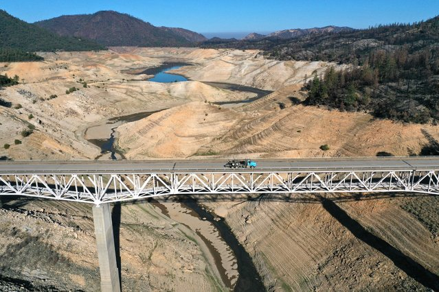 In an aerial view, the Enterprise Bridge crosses over a section of Lake Oroville that was previously underwater on July 22, 2021 in Oroville, California. As the extreme drought emergency continues in California, Lake Oroville's water levels are continuing to drop to 28 percent of capacity. State water officials say that Lake Oroville's Edward Hyatt Powerplant might be forced to shut down the hydroelectric plant as soon as August or September if water levels continue to drop. (Photo by Justin Sullivan/Getty Images)