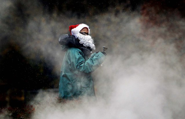 As freezing rain falls, Tyshun Lindsey, 15, donning a Santa hat and beard rings a bell to get drivers' attention while selling bags of pecans in Memphis, on December 6, 2013. (Photo by Mark Weber/Commercial Appeal)