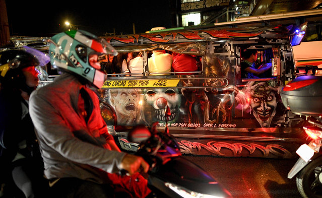 This picture taken on January 14, 2019 shows custom artwork on the side of a jeepney during rush hour in Manila, Philippines. (Photo by Noel Celis/AFP Photo)