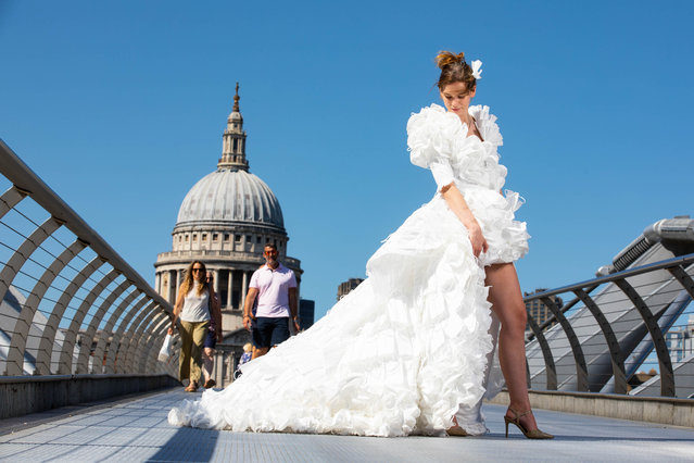 Jemima Hambro models, on the Millennium Bridge in London on Monday July 19, 2021, a wedding dress designed by Tom Silverwood and made from over 1,500 unwanted face masks, for wedding planning website, Hitched, to celebrate all restrictions on weddings lifting in England from Monday. (Photo by David Parry/PA Images via Getty Images)