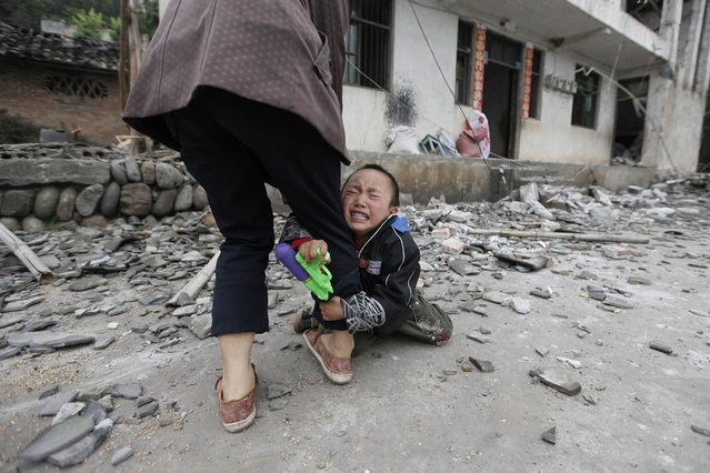 A boy holds his mother's leg as he cries in front of their damaged house after a strong 6.6 magnitude earthquake at Longmen village, Lushan county in Ya'an, Sichuan province. (Photo by Jason Lee/Reuters)