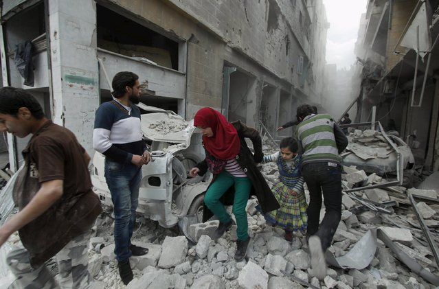 A woman holds the hand of a girl as they rush away from a site hit by what activists said was an airstrike by forces loyal to Syria's President Bashar al-Assad in Aleppo's al-Fardous district April 14, 2015. (Photo by Rami Zayat/Reuters)