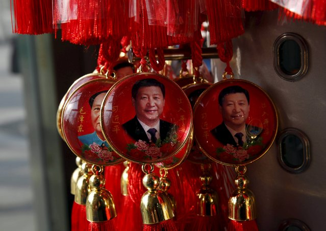 Pendants bearing the images of China's President Xi Jinping (C and R) and Chinese late chairman Mao Zedong are displayed at a shop near the Great Hall of the People, where the National People's Congress will be held, in Beijing, China, February 26, 2016. President Xi Jinping has emerged as one of China's strongest leaders since Mao Zedong, presiding over an unprecedented anti-corruption drive, a sweeping crackdown on political dissent, and a carefully crafted media campaign to build a man-of-the-people cult of personality around himself. (Photo by Kim Kyung-Hoon/Reuters)