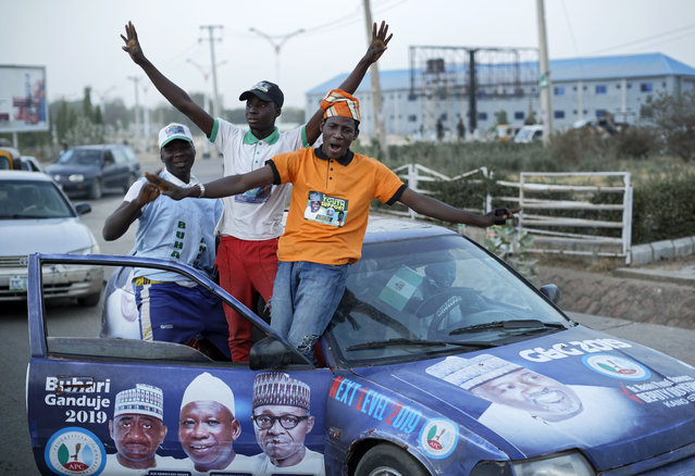 Youth supporters of President Muhammadu Buhari cheer as they return from a rally of the ruling All Progressives Congress party, near the offices of the Independent National Electoral Commission in Kano, northern Nigeria Thursday, February 14, 2019. Nigeria's main opposition party charged Thursday that the election commission has kept more than 1 million ghost voters on the national register, raising fears of vote rigging ahead of Saturday's presidential election. (Photo by Ben Curtis/AP Photo)