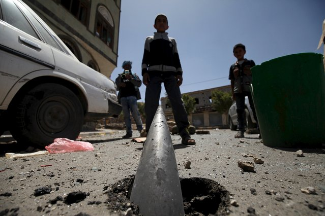 Boys stand in front of an artillery shell partially buried in the ground along a street damaged by an air strike on Monday that hit a nearby army weapons depot, in Sanaa April 21, 2015. (Photo by Mohamed al-Sayaghi/Reuters)
