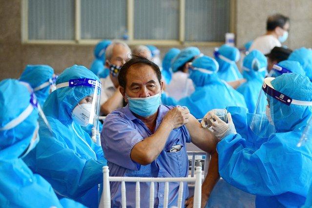 A man (C) receives the AstraZeneca Covid-19 coronavirus vaccine in Hanoi on September 10, 2021. (Photo by Nhac Nguyen/AFP Photo)