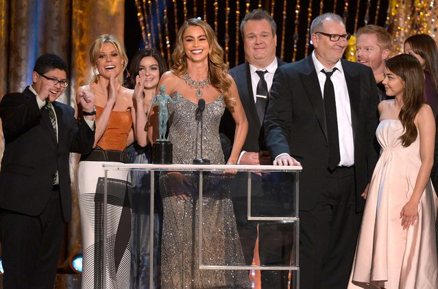 """(L-R) Rico Rodriguez, Julie Bowen, Ariel Winter, Sofia Vergara, Eric Stonestreet, Ed O'Neill, Jesse Tyler Ferguson, and Sarah Hyland accept the Outstanding Performance by an Ensemble in a Comedy Series award for """"Modern Family"""". (Photo by Kevork Djansezian/Getty Images)"""