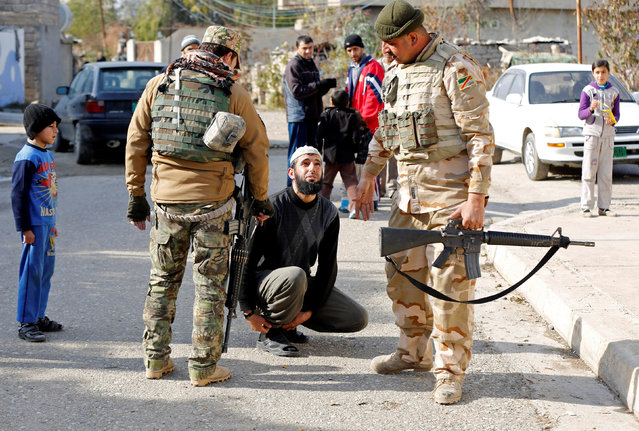 Members of the Iraqi army stand next to a man whose trousers need to be shortened according to Islamic State's tradition, in the Arabi neighborhood in Mosul, Iraq January 26, 2017. (Photo by Muhammad Hamed/Reuters)