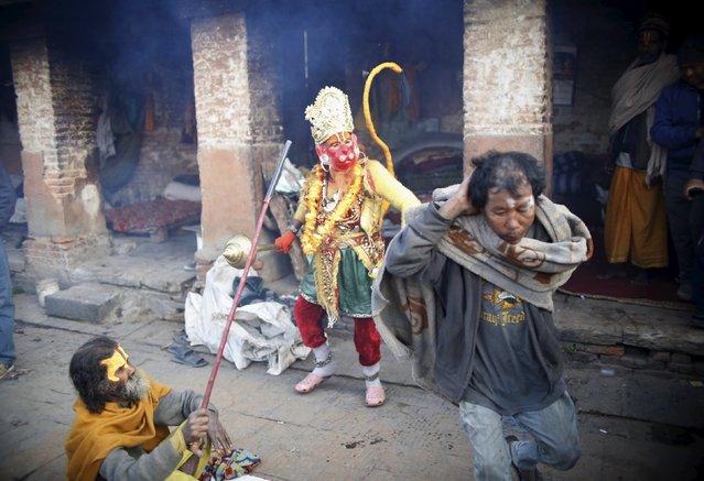 Hindu holy men, or sadhus, chase a person (R) disturbing them during the Shivaratri festival at the premises of Pashupatinath Temple in Kathmandu, Nepal, March 7, 2016. (Photo by Navesh Chitrakar/Reuters)