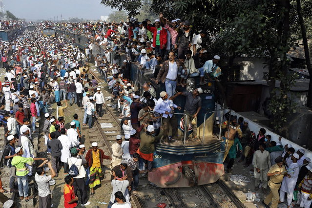 Bangladeshi railway police try to clear line, as thousands of Bangladeshi Muslims gather to board trains to return home  after attending three-day Islamic Congregation on the banks of the River Turag in Tongi, 20 kilometers (13 miles) north of the capital Dhaka, Bangladesh, Sunday, January 26, 2014. (Photo by A. M. Ahad/AP Photo)