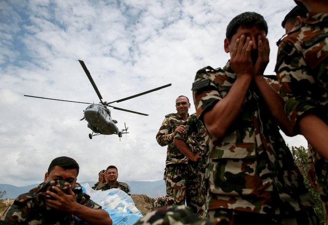 Nepal Army personnel take cover as an Indian Airforce helicopter evacuating injured residents takes off following Saturday's earthquake in Sindhupalchowk, Nepal, April 28, 2015. (Photo by Danish Siddiqui/Reuters)