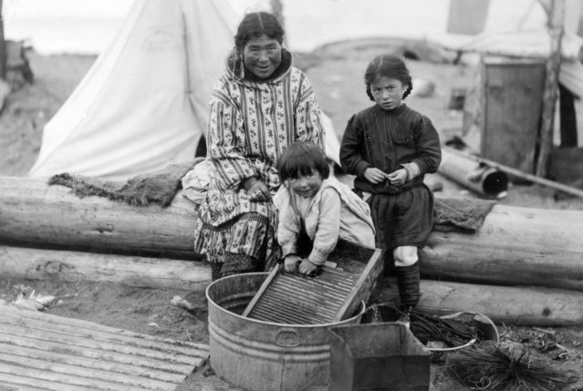 People, Alaska, circa 1920. Eskimo children helping their mother on washing day. (Photo by Popperfoto/Getty Images)