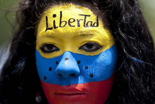 "An opposition demonstrator, her face painted with the colors of the Venezuelan national flag and the word ""Freedom"" on her forehead, participates in the May Day march in Caracas, Venezuela, Friday, May 1, 2015. Pro-government and opposition workers marched today in the midst of the political and economic crisis prevailing in the country, with separate marches that took place to mark International Workers Day also known as May Day. (Photo by Ariana Cubillos/AP Photo)"