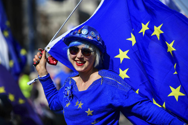 Madeleina Kay, Young European of the Year 2018 dressed in blue holds an EU flag and entertains the public while singing about Brexit outside the Houses of Parliament in Westminster, London, ahead of the latest round of debates in the House of Commons concerning Brexit issues, Monday April 1, 2019. (Photo by Rebecca Brown/PA Wire via AP Photo)