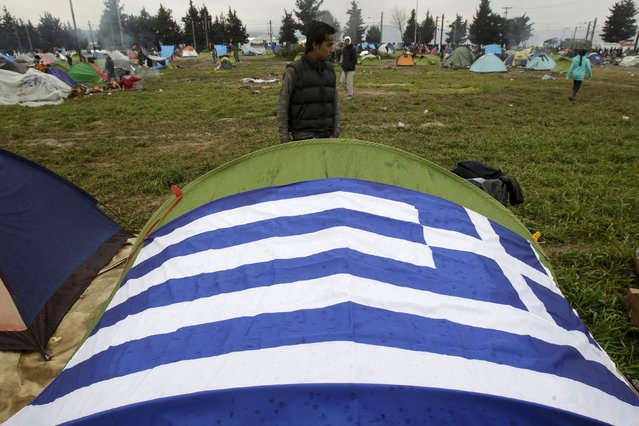 A Greek national flag is laid on a tent at a makeshift camp for refugees and migrants at the Greek-Macedonian border, near the village of Idomeni, Greece March 16, 2016. (Photo by Alkis Konstantinidis/Reuters)