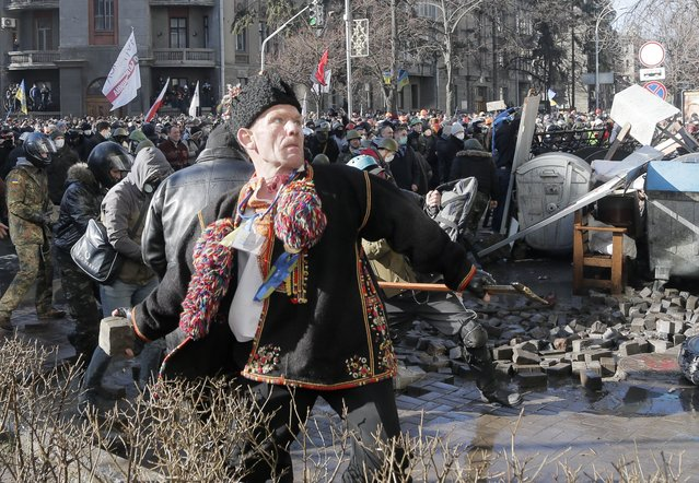 An anti-government protester dressed in  Ukrainian national dress throws a stone during clashes with riot police outside Ukraine's parliament in Kiev, Ukraine, Tuesday, February 18, 2014. (Photo by Efrem Lukatsky/AP Photo)