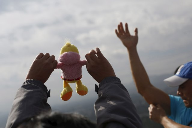 A woman holds up a soft toy towards the sun to welcome the spring equinox while standing on the Pyramid of the Sun in the pre-hispanic city of Teotihuacan, on the outskirts of Mexico City, Mexico, March 20, 2016. (Photo by Edgard Garrido/Reuters)