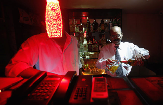 A bartender pours Haywards 5000 strong beer, a product of SABMiller, into a glass at a restaurant in Mumbai August 28, 2013. (Photo by Danish Siddiqui/Reuters)