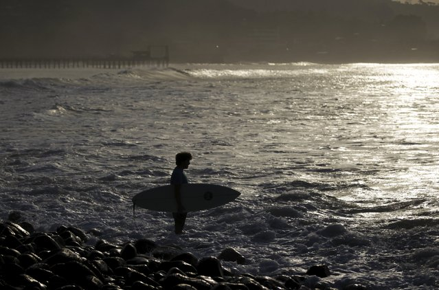 A surfer prepares to get in the water at Punta Roca Beach in La Libertad May 13, 2015. (Photo by Jose Cabezas/Reuters)