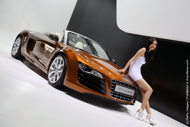 A s*xy model stands beside Audi R8 5.2 quattro car
