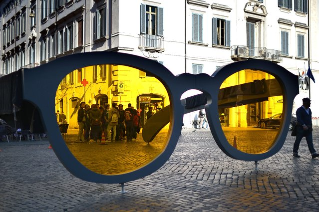 Pedestrians pass by giant sunglasses on Piazza Farnese in downtown Rome as part of an advertising campaign on March 12, 2014. (Photo by Gabriel Bouys/AFP Photo)