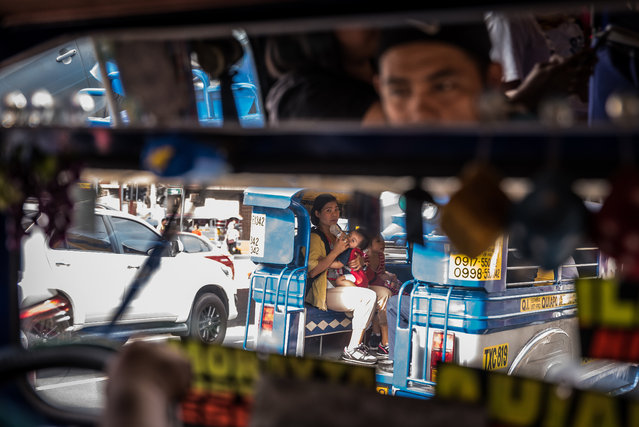 """Markun says he likes to drive """"fast and furious"""". One of his passengers jokes """"we all go to heaven"""". He has driven a jeepney for 15 years. He hopes that the phasing out of jeepneys won't happen that soon, as he loves his job. (Photo by Claudio Sieber/Barcroft Media)"""