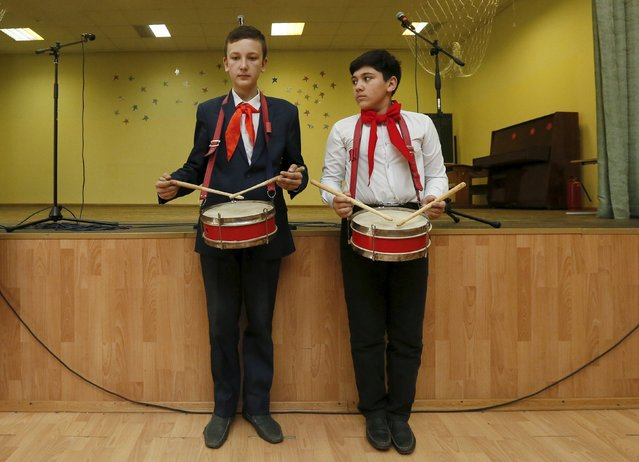 Children, wearing red neckerchiefs, a symbol of the Young Pioneer Organisation, play the drums during a ceremony for the inauguration of 45 newly adopted members on the day of its anniversary at school-lyceum number 12 in the Siberian city of Krasnoyarsk, Russia, May 19, 2015. (Photo by Ilya Naymushin/Reuters)