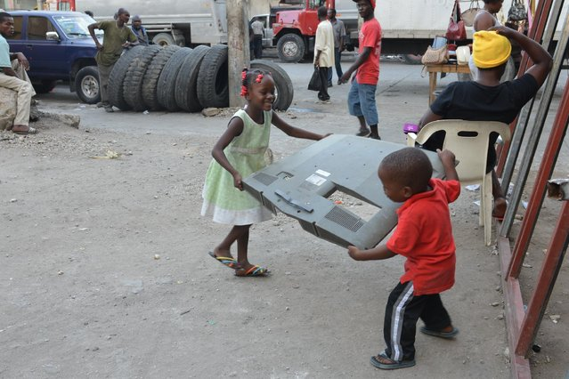 In this April 4, 2016 photo, children play with a piece of a broken television outside sculptor Andre Eugene's open-air museum and art workshop off a trash-strewn street cutting through some of the poorest neighborhoods in Port-au-Prince, Haiti. Andre Eugene a founding member of a loose collective of Haitian artists called Atis Rezistans who have become celebrated in the international art world by creating sculptures out of scrapped car parts, old wood, discarded toys and even human skulls found scattered outside crumbling mausoleums. (Photo by David McFadden/AP Photo)