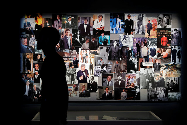 """A visitor looks at a wall filled with photographs during the press visit of the exhibition """"The Designing 007: Fifty Years of Bond Style"""" at the Grande Halle de la Villette in Paris, France, April 13, 2016. (Photo by Benoit Tessier/Reuters)"""