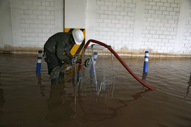 A man works in a flooded commercial center access in Santiago, April 17, 2016. (Photo by Ivan Alvarado/Reuters)