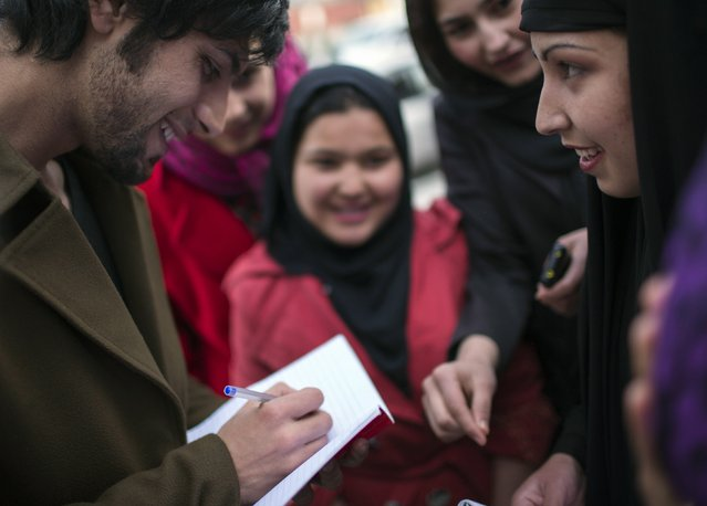 Afghan pop singer Arash Barez signs a notebook for his fan after his concert at a ceremony to mark International Women's Day in the Kabul-Dubai wedding hall in Kabul March 8, 2014. (Photo by Morteza Nikoubazl/Reuters)