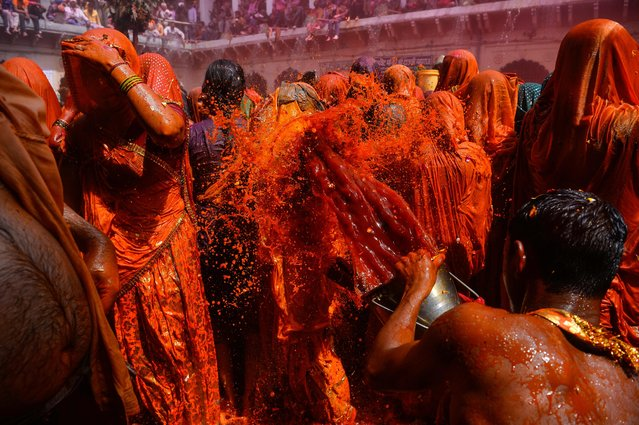 """Indian revellers take part in the game of """"Huranga"""" at The Dauji Temple in Mathura, some 100 kms south of New Delhi on March 14, 2017. (Photo by Chandan Khanna/AFP Photo)"""
