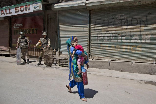 A Kashmiri Muslim woman carries a child as she walks past Indian paramilitary soldiers standing guard outside a closed market area during a strike in Srinagar, Indian-controlled Kashmir, Saturday, June 27, 2015. (Photo by Dar Yasin/AP Photo)