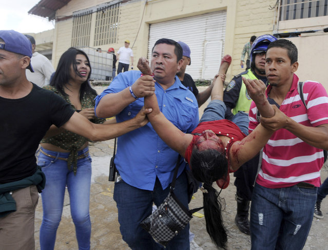 A woman is carried away after she was injured when a march belonging to the National Front for Popular Resistance (FNRP) clashed with another march that was supporting the current President Juan Orlando Hernandez in Tegucigalpa, Honduras, Sunday, June 28, 2015. (Photo by Fernando Antonio/AP Photo)