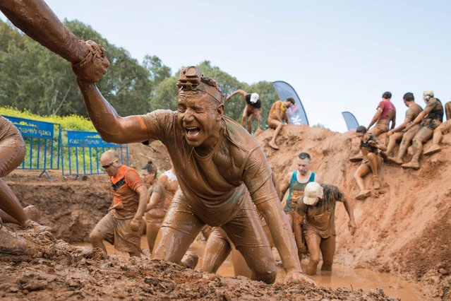 Participants take part in the Mud Day race, a 13km obstacle course, on March 24, 2017 in the Israeli Mediterranean coastal city of Tel Aviv. (Photo by Jack Guez/AFP Photo)