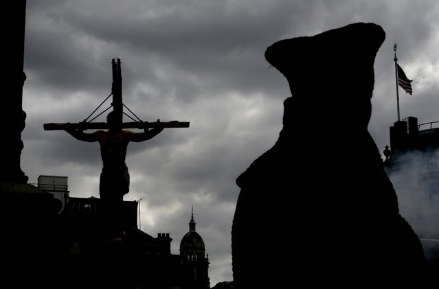 "An actor is silhouetted hanging on a cross during a performance in Trafalgar Square in London, Friday, April 18, 2014. The play called ""The Passion of Jesus"" was a free performance depicting the betrayal, capture, trial, crucifixion and resurrection of Jesus, performed by the Wintershall players. (Photo by Kirsty Wigglesworth/AP Photo)"