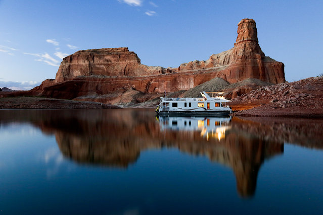 """""""Camping in Style"""". Camping at Lake Powell is an fairly regular tradition in my family, and this time I decided to take my camera along. This shot was taken a little bit after sunset, and while it's usually very hard for me to tear myself away from the campfire (smores!) at the end of the day, it was pretty cool to get a shot of our boat against the very distinctive red rock and blue water of the lake. Photo location: Lake Powell, Utah, USA. (Photo and caption by Ritu Vincent/National Geographic Photo Contest)"""